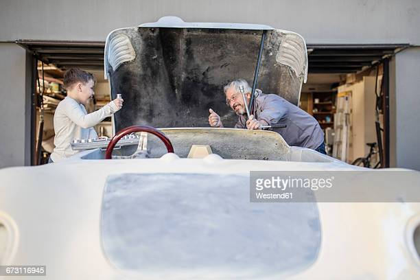 Senior man and boy working on old car together