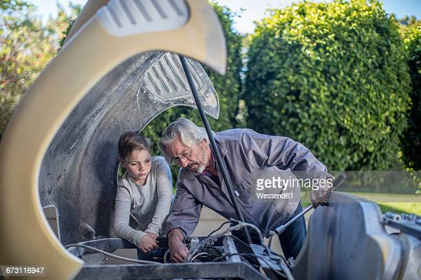 senior man and boy working on old car together - vintage auto repair stock pictures, royalty-free photos & images