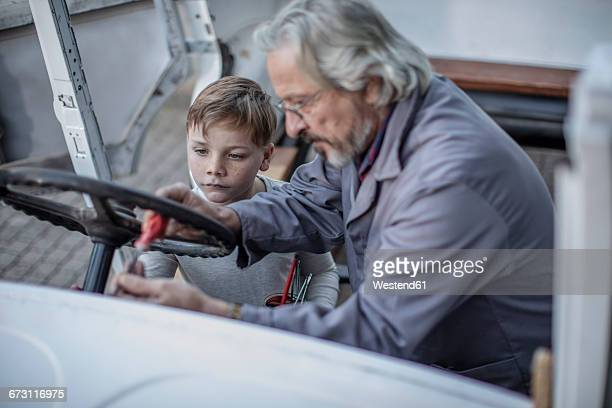 Senior man and boy working on steering wheel of a car
