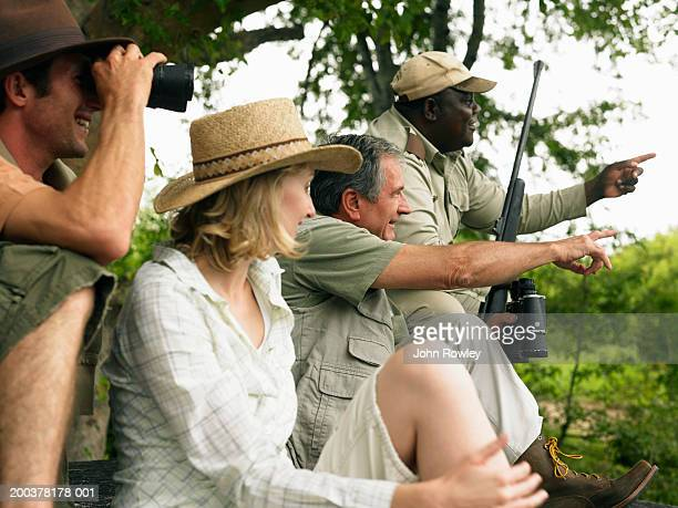 Senior man and couple on safari with guide, smiling