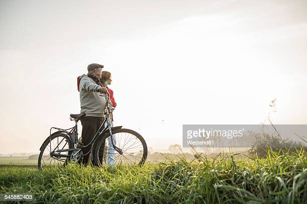 Senior man and daughter in rural landscape with bicycle