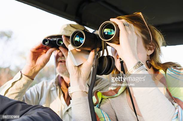 Senior man and daughter looking out through binoculars on safari, Kafue National Park, Zambia