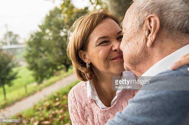 Senior man and daughter rubbing noses