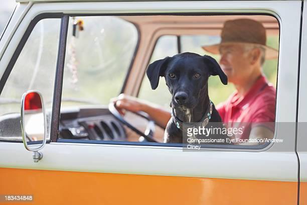 Senior man and dog in camper van