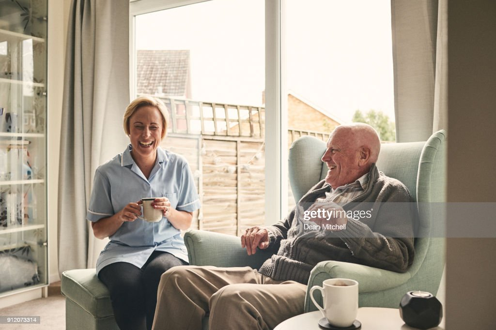 Senior man and female carer enjoying coffee at home : Stock Photo