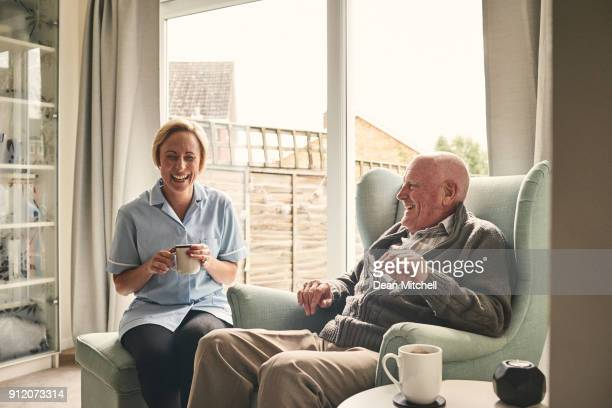 senior man and female carer enjoying coffee at home - old stock photos and pictures