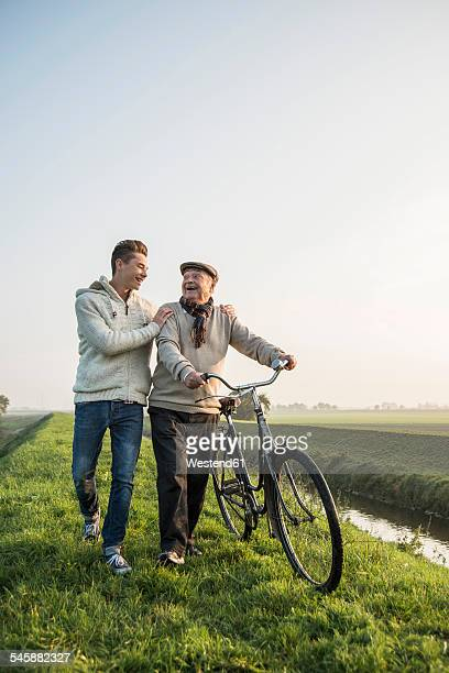 Senior man and grandson in rural landscape with bicycle