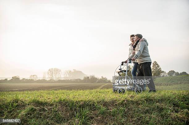 Senior man and grandson in rural landscape with wheeled walker