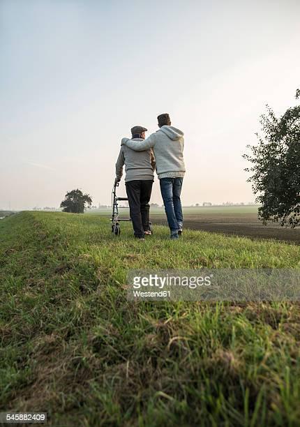 Senior man and grandson in rural landscape with wheeled walker