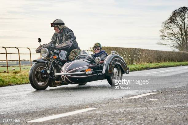 senior man and grandson riding motorcycle and sidecar along rural road - motorbike stock photos and pictures