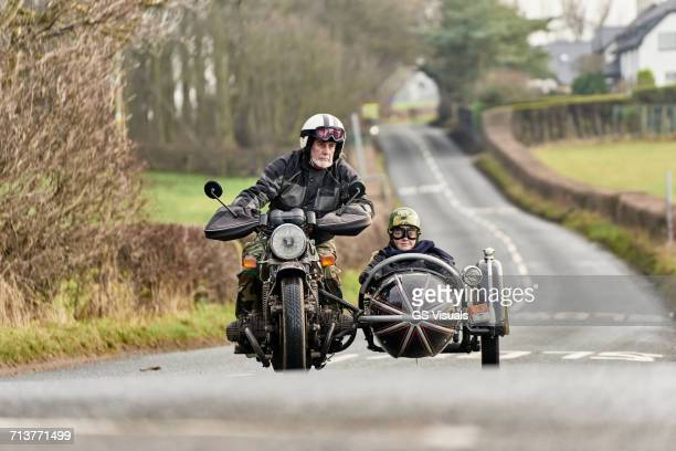 Senior man and grandson riding motorcycle and sidecar on rural road