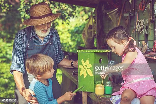 Senior man and his grandchildren make birdhouse