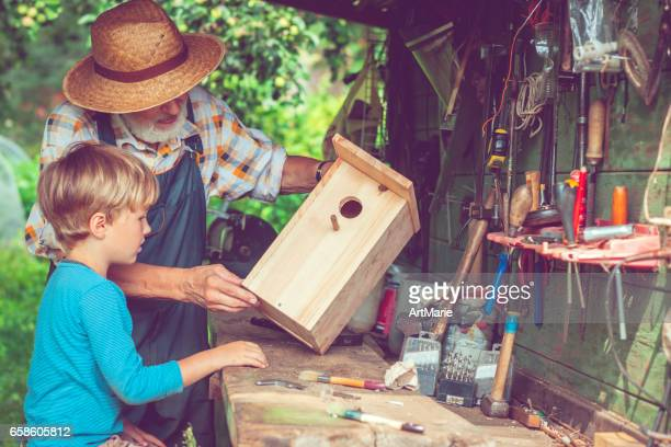 senior man and his grandson make birdhouse - birdhouse stock pictures, royalty-free photos & images