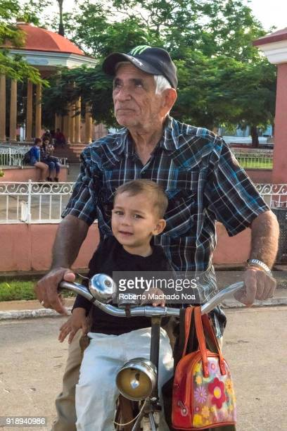 Senior man and his grandson on a bicycle They watch the progress in the works of the Light Display of the San Salvador district