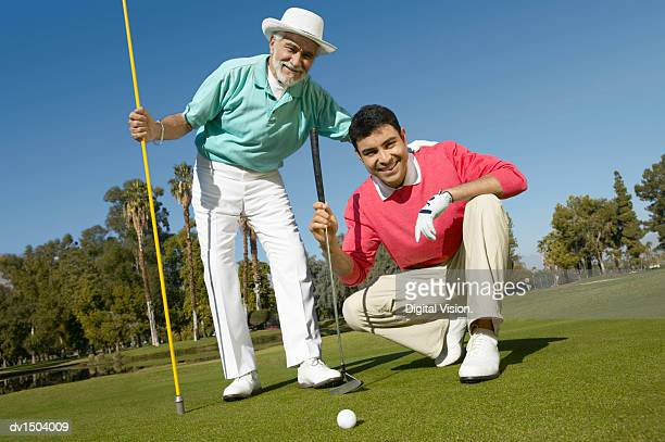 Senior Man and His Mature Son on a Putting Green, Holding the Golf Flag and Looking at the Golf Ball