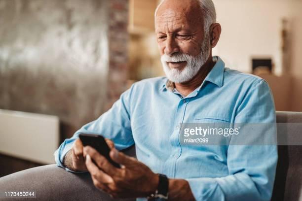 senior man and his smartphone - uomini anziani foto e immagini stock