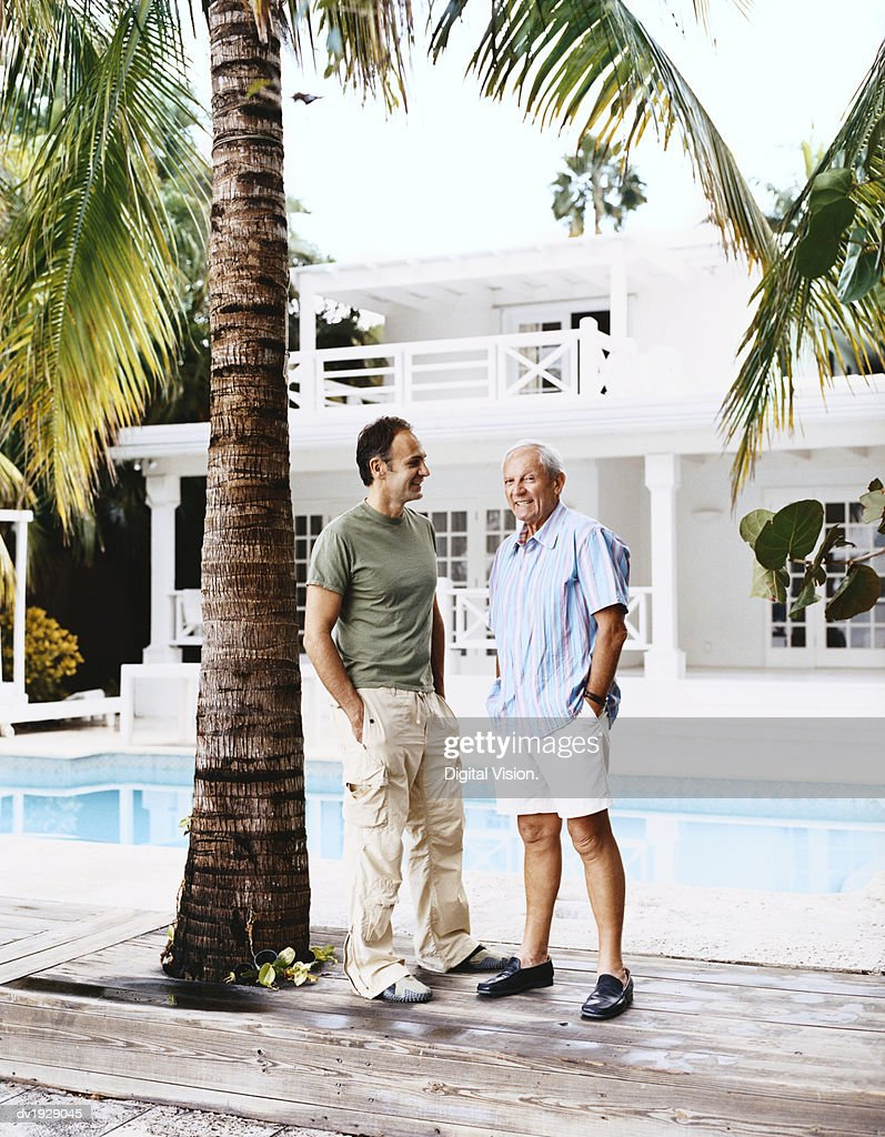 Senior Man and His Son Stand Talking by a Swimming Pool Outside Their House : Stock Photo