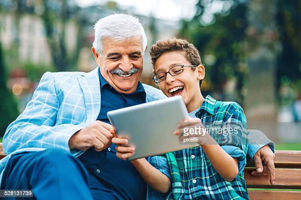 Senior man and little boy with digital tablet