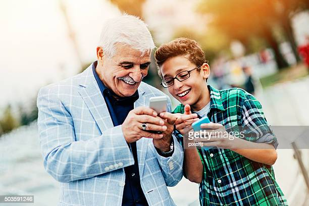 Senior man and little boy with smart phone outdoors