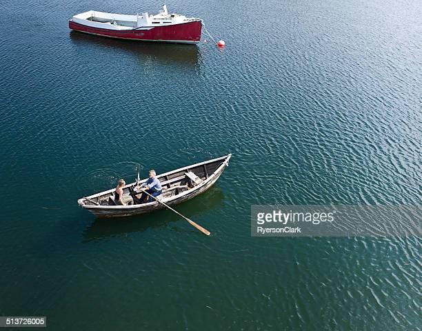 Alter Mann, ältere Frau in einem Dory Row Boot.
