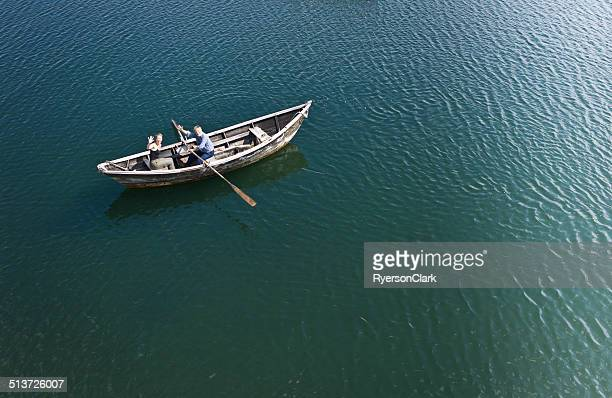 senior man and mature woman in a dory row boat. - rowing boat stock pictures, royalty-free photos & images