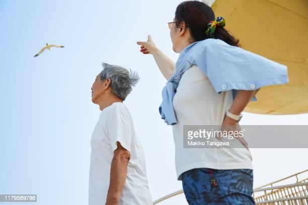 senior man and mature woman on sunny beach - makiko tanigawa ストックフォトと画像