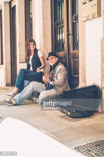 Senior Man and Mature Woman Street Artists Playing Electric Guitar and Singing