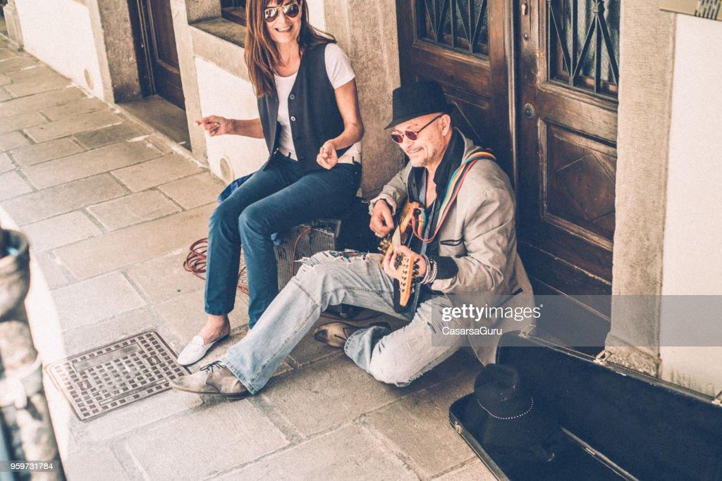 Ältere Mann und Reife Frau Straßenkünstler spielen e-Gitarre und Gesang : Stock-Foto