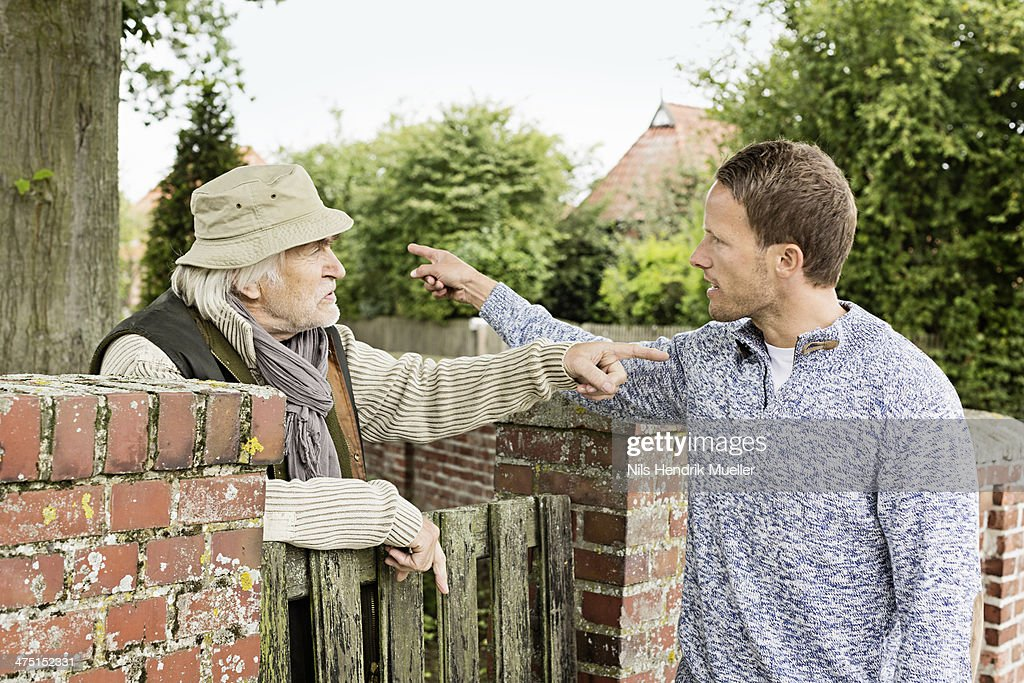 Senior man and mid adult man arguing : Stock Photo