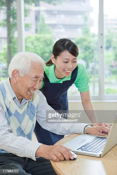 Senior man and nurse using a laptop, Kanagawa Prefecture, Honshu, Japan