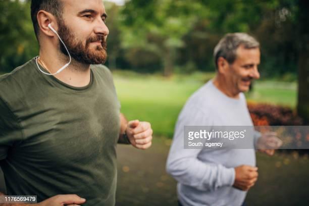 homem sênior e filho que movimentam-se no parque - adulto de idade mediana - fotografias e filmes do acervo