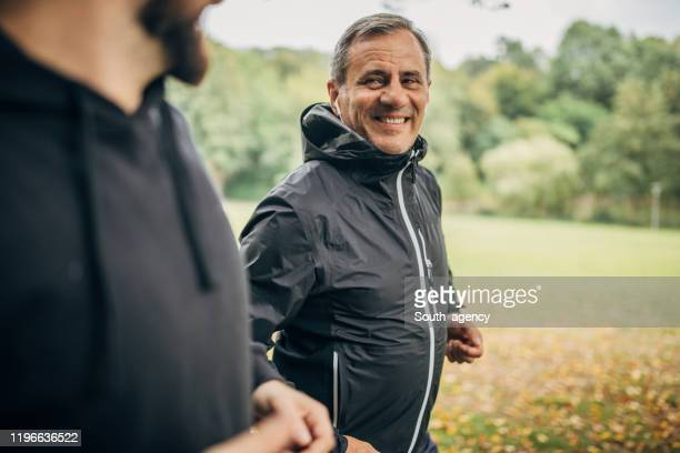 senior man and son jogging together in park - windbreak stock pictures, royalty-free photos & images