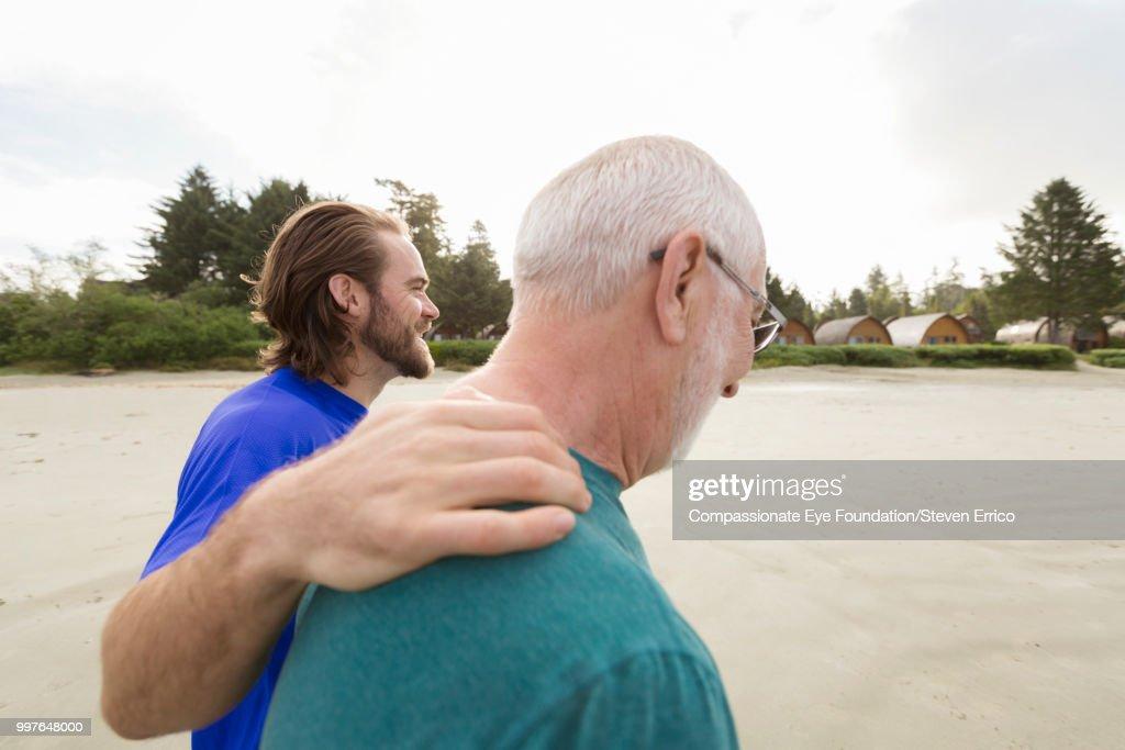 Senior man and son walking on beach : Stock-Foto