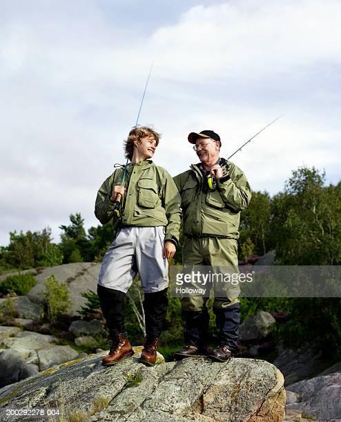 Senior man and teenage grandson (13-15) holding fishing rods outdoors