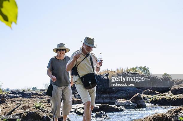 Senior man and wife exploring river rocks, near Victoria Falls, Zambia