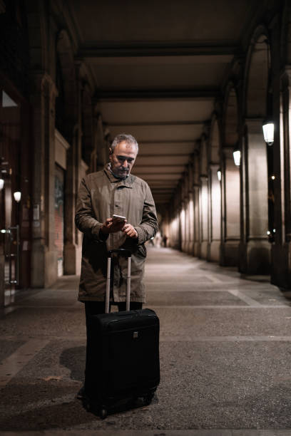 Senior man and with travel suitcase is checking smartphone at night under a beautiful city arcade in European city. Traveling in old age
