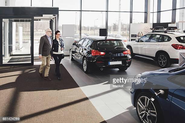 Senior man and woman entering in car showroom