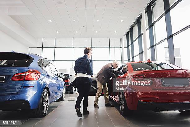 senior man and woman examining car at showroom - showroom stock pictures, royalty-free photos & images