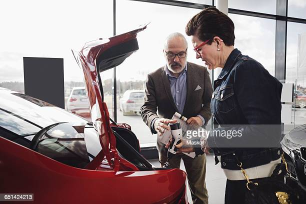 Senior man and woman examining charger of electric car at showroom