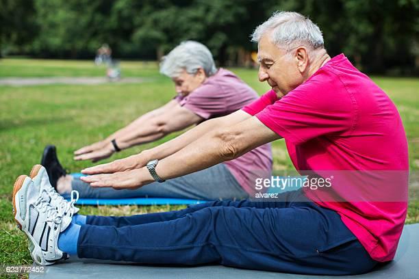 Senior man and woman exercising at the park