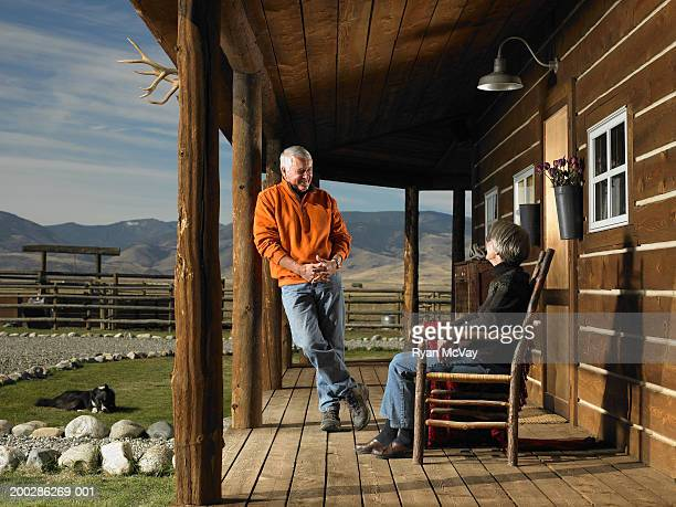 senior man and woman having conversation on porch, smiling - bozeman stock pictures, royalty-free photos & images