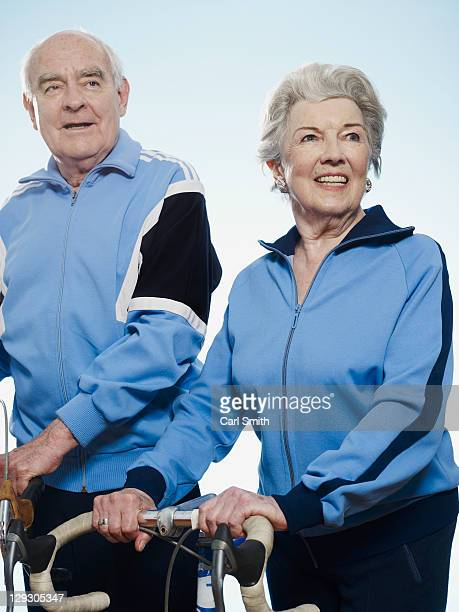 Senior man and woman in sportswear holding bicycles