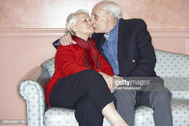 Senior man and woman kissing and holding hands on sofa