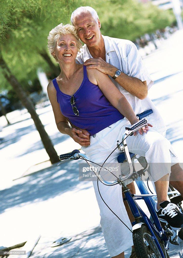 Senior man and woman on tandem bike, portrait. : Stockfoto