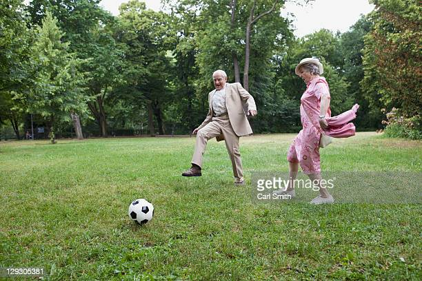 Senior man and woman play football in the park