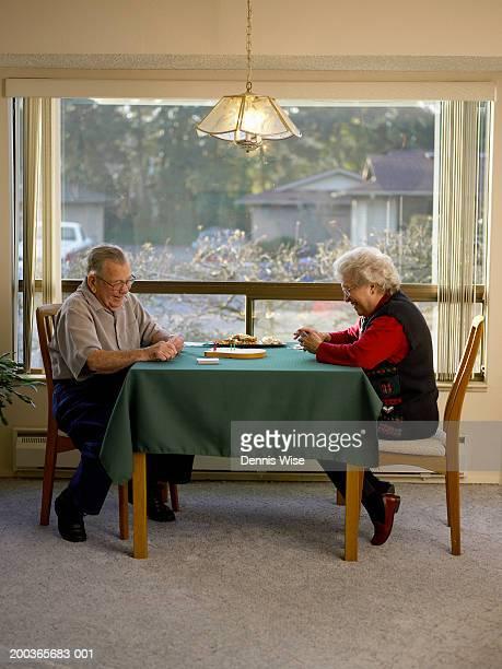 senior man and woman playing cribbage, side view - carta de baralho jogo de lazer - fotografias e filmes do acervo