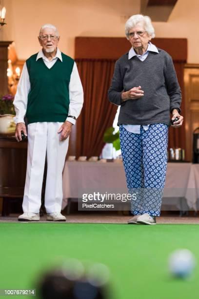 Senior man and woman playing indoor bowls