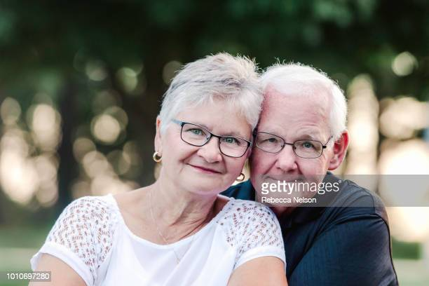 senior man and woman posing for camera