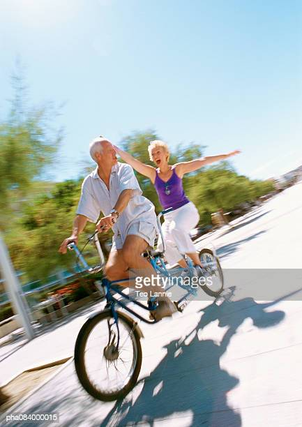 Senior man and woman riding together on tandem bike, blurred.