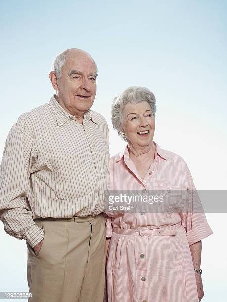 Senior man and woman side by side looking amused
